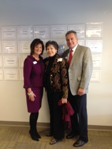 Kathy Lambert, CEO and Co-Founder. Nadine Boon, VP Commercial, Thomas Realty Group, LLC and Brad Lambert, COO and Co-Founder in front of Corporate Donor plaques.